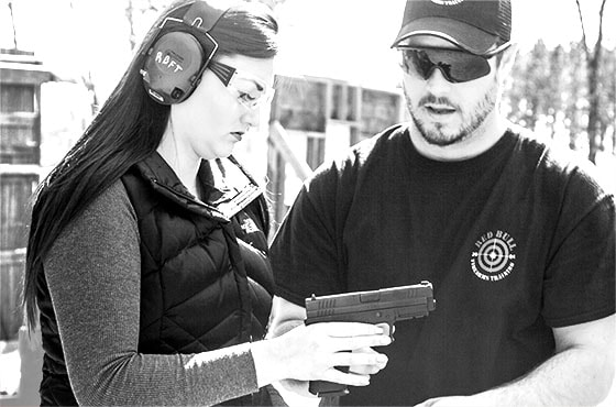 Firearms instructor with student explaining handgun functionality