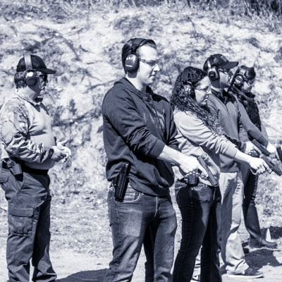 Firearms Instructor helps students on the shooting range at Defensive Handgun training